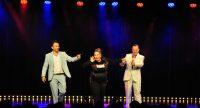 Publikum blickt auf die Bühne, dort sind zwei Männer und eine Frau zu sehen, Quelle: DTF Stuttgart