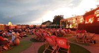 Konzertsituation Open-Air bei Sonnenuntergang. Mehrere Liegen sind zu sehen, links auf der Bühne spielt eine Musikgruppe., Quelle: DTF Stuttgart