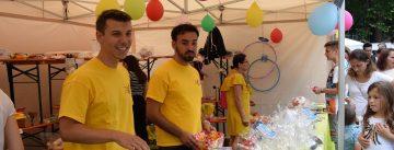 Zwei junge Männer in gelben Shirts stehen hinter einem Marktstand mit Geschenken, Quelle: DTF