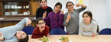 Lachende Kinder stehen hinter einem Tisch mit Gemüsehäppchen und Schnittchen, Quelle: DTF